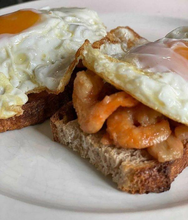 langostinos al ajillo y manzanilla con huevo frito en hogaza de pan